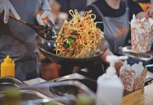 noodles being fried in pan in Asia