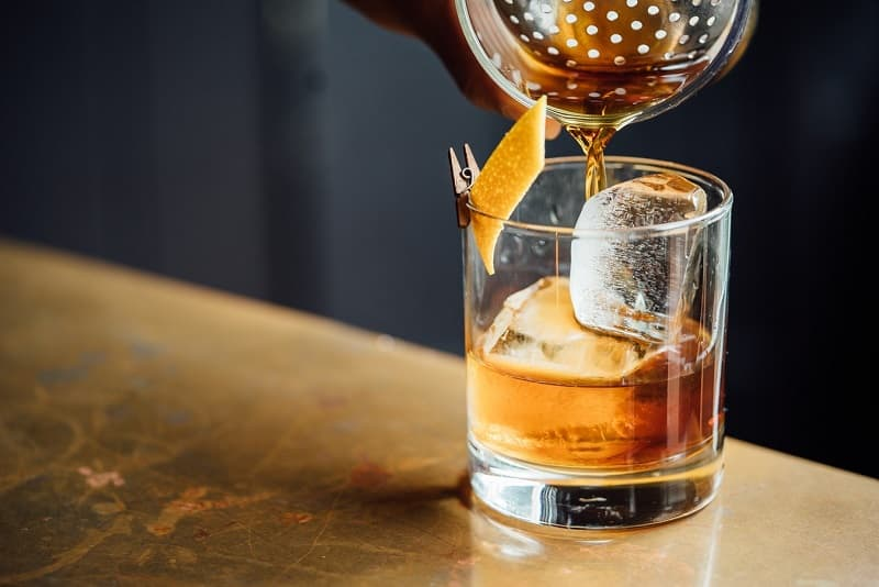 rum drink being poured into rocks glass